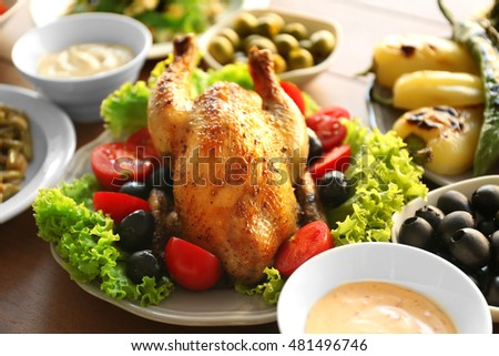 Plates with roasted chicken and different salads on table