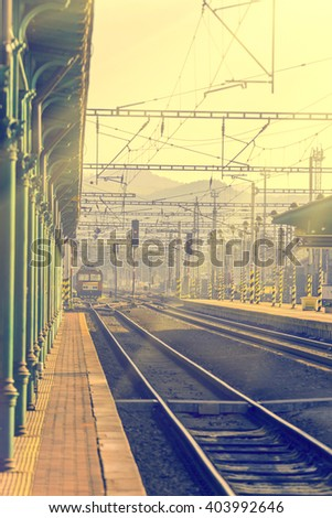 Platform and railroad tracks with a train in the distance. Sunlight