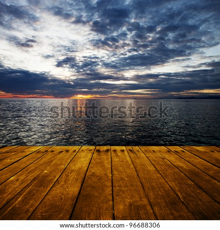 platform beside sea with sunset - stock photo