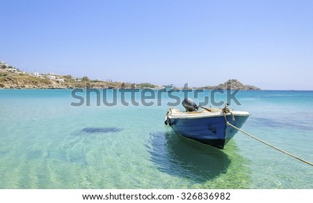 Platis Gialos beach on greek island Mykonos, Greece. A view of the crystal clear blue sea and a boat tied in the water on a summer day. - stock photo
