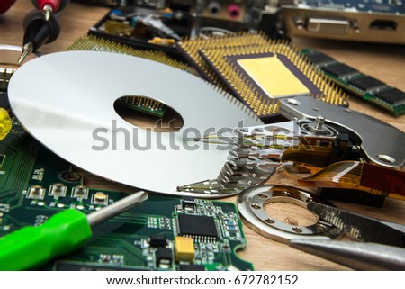 platter, actuator arm and board from disassembled HDD with tools in PC service