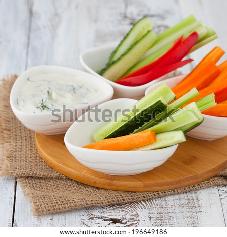 Platter of assorted fresh vegetables with yogurt dip on white wooden background, selective focus - stock photo