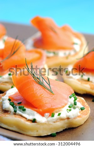 Platter of bite size smoked salmon appetisers canapes suitable for a party  - stock photo