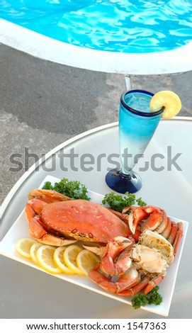Platter of crab with lemons and parsley and a glass of sparkling water out by the poolside - stock photo