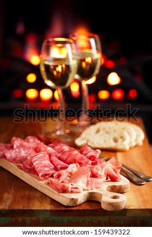 Platter of serrano jamon Cured Meat with cozy fireplace and wine background - stock photo