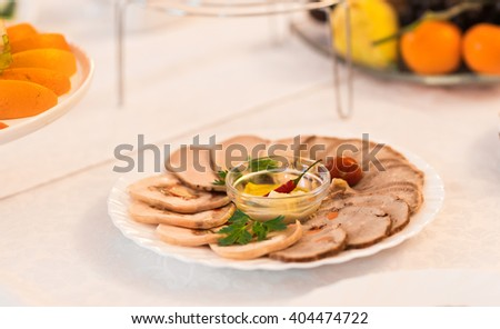 platter of sliced ham,salami and cured meat with vegetable decoration on festive table - stock photo