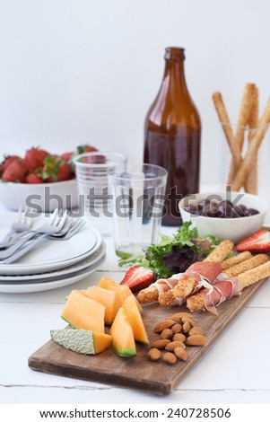 Platter of snacks finger food, prosciutto parma ham wrapped bread sticks with rock melon slices and a bowl of strawberries - stock photo