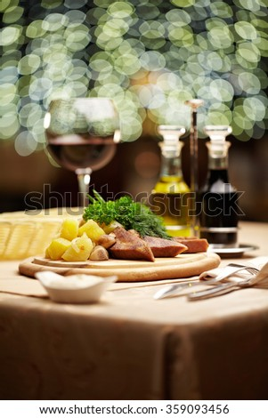 Platter with beef, cottage fries, side salad and a glass of wine - stock photo