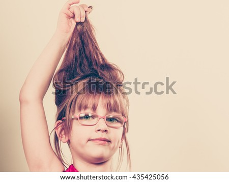 Play and fun. Charming little girl making funny crazy hair. Smiling lovely cute female child wearing glasses. Positive facial emotion. - stock photo
