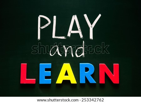 Play and learn concept, colorful words on blackboard - stock photo