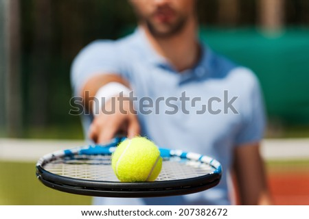 Play with me! Close-up of young man in polo shirt holding tennis ball on his racket while standing on tennis court