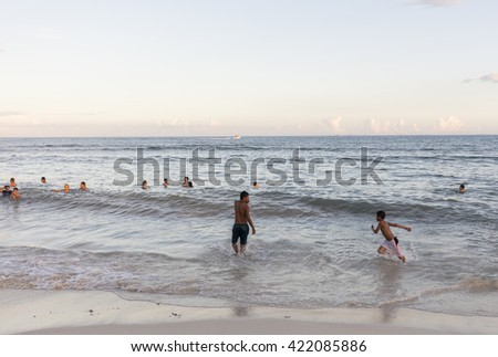 Playa del Carmen, Mexico - January 5 2016 - People on the beach in Playa del Carmen at sunset. The city boasts a wide array of tourist activities due to its geographical location in the Riviera Maya.