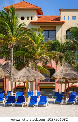 PLAYA DEL CARMEN, MEXICO - JULY 13, 2011: Deck chairs on the beach of Playacar at Caribbean Sea of Mexico. This resort area is popular destination with the most beautiful beaches.