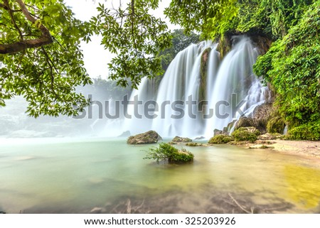 Played with the moss rock waterfall Ban Gioc with lakeside tree foreground, smooth flow of water, creating a waterfall down the white silk sheet side high mountains, sunny yellow iridescent great lake - stock photo