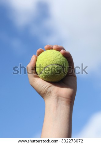 Player Gripping a Yellow Tennis Ball Against a Blue Sky  - stock photo