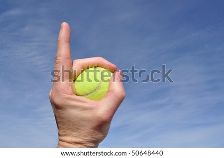 Player Gripping a Yellow Tennis Ball Doing Number One Sign