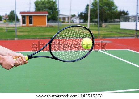 Player hands on tennis racket hitting a back hand volley - stock photo