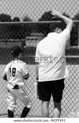 player watching the baseball game beside the coach - stock photo