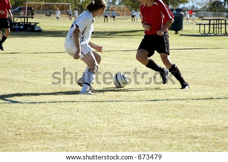 Players position themselves for control of the ball in a girl's soccer game. - stock photo