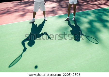 Players shadows on the tennis court - stock photo