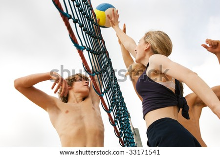 Players trying to block a dangerous attack in a beach volleyball game - stock photo