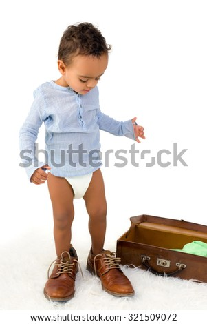 Playful African toddler boy having fun with Dad's shoes - stock photo