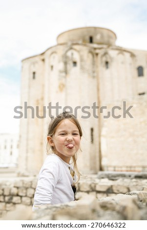 Playful and carefree cute little Caucasian girl making faces, looking at mum and dad.  - stock photo