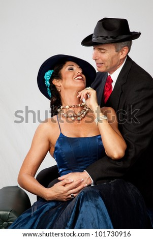 Playful and romantic couple, in formal dress for an event,  in a loving mood