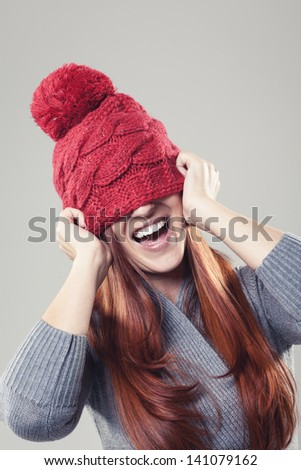 Playful and smiling pretty woman wearing a red winter beanie with bobble stuck to her nose covering the eyes - stock photo