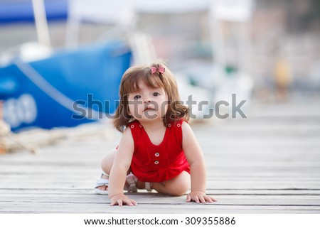 playful baby girl crawling. sea style. outdoors. happy child. Baby in sea sailor style. Happy child sitting on wooden floor outdoors