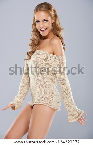 Playful beautiful blonde woman in a skimpy jersey laughing as she looks back over her shoulder with a teasing glance - stock photo