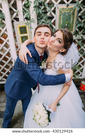 Playful beautiful bride and groom posing outdoors at their wedding day. Close-up - stock photo