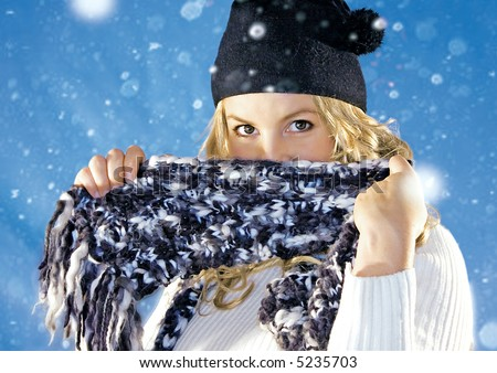 Playful blond girl is hiding behind her scarf. keyword for this collection is: snowmakers77 - stock photo