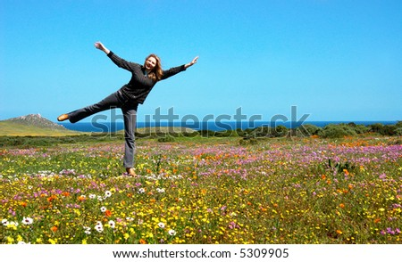 Playful blonde woman in the field full of flowers - stock photo
