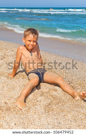 playful boy on the beach with sea on background - stock photo