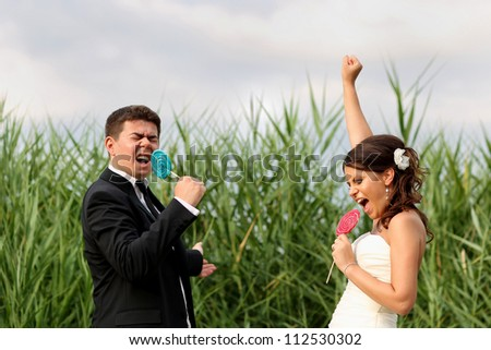 playful bride and groom with lollipop in a field landscape - stock photo