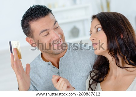 Playful couple arguing over on-line shopping - stock photo