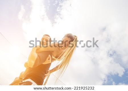playful couple. boyfriend takes his girl on the shoulder. both smiling at the camera - stock photo