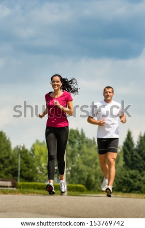 Playful couple friends running a race in a park