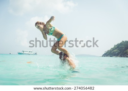 playful couple in the water. woman jumping in the water from the man shoulders. concept about vacations, fun and people - stock photo