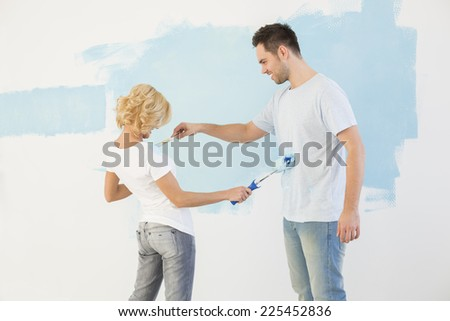 Playful couple painting each other in new house - stock photo