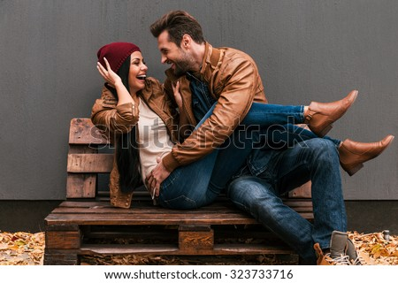 Playful couple. Playful young loving couple having fun together while sitting on the wooden pallet together with grey wall in the background and fallen leaves on ht floor - stock photo