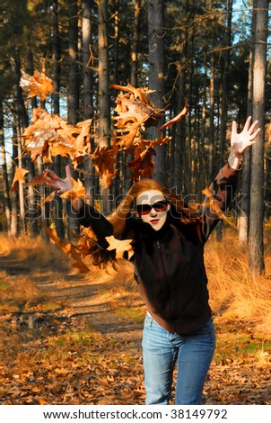 playful dutch girl throwing autumn leaves in the forest - stock photo