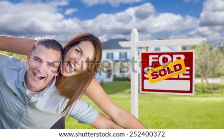 Playful Excited Military Couple In Front of Home with Sold Real Estate Sign. - stock photo
