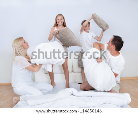 Playful Family Having A Pillow Fight Together On Bed In Bedroom - stock photo