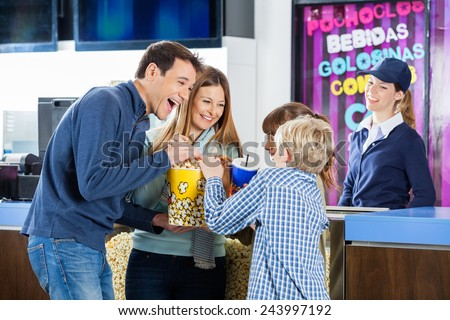 Playful family of four enjoying snacks while female worker standing at cinema concession stand - stock photo