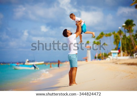 playful father and son having fun on tropical beach - stock photo