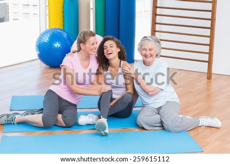 Playful female friends sitting together on exercise mat in gym - stock photo