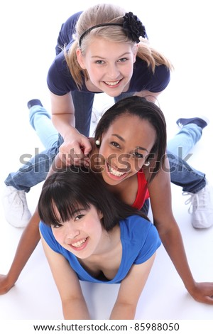 Playful fun by three multi cultural teenage school student friends made up of mixed race african american, oriental Japanese and caucasian all with big smiles having a laugh. - stock photo