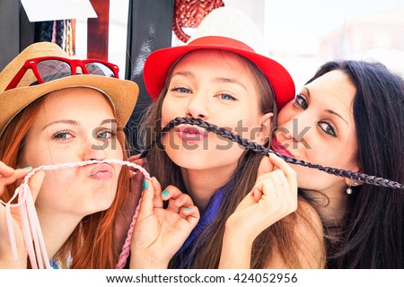 Playful girlfriends funny faces selfie with fake mustache at street market - Beautiful girls having fun during shopping day in old town - Concept of carefree youth -  Main focus on middle subject - stock photo